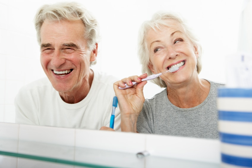Senior Couple In Bathroom Brushing Teeth Laughing