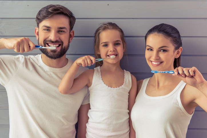 Beautiful young parents and their cute little daughter are looking at camera and smiling while brushing teeth, against gray wall
