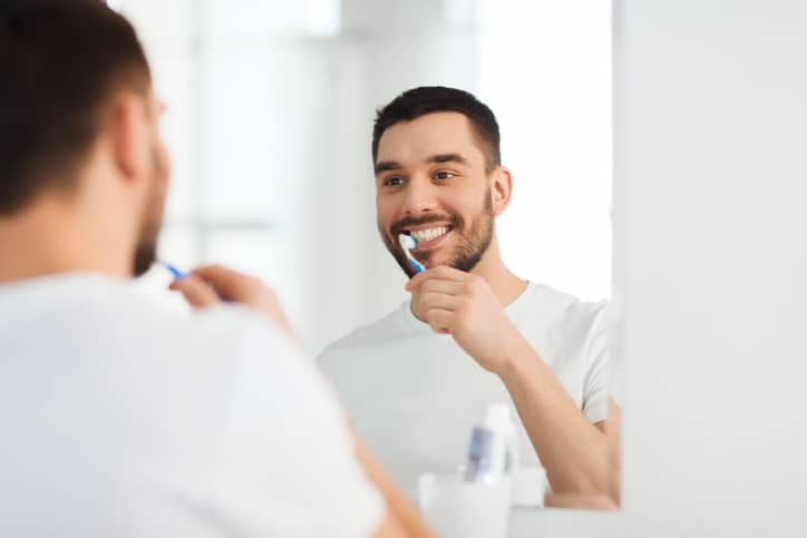 health care, dental hygiene, people and beauty concept - smiling young man with toothbrush cleaning teeth and looking to mirror at home bathroom